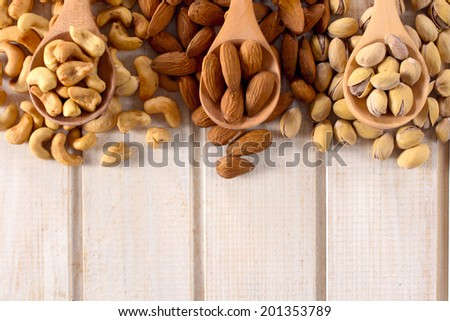 Nuts mix in the wooden ladles from above and blank space below  - stock photo