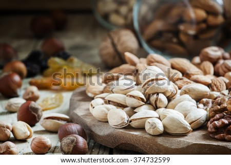 Nuts mix of pistachios, hazelnuts, walnuts and almonds on a wooden platter, selective focus