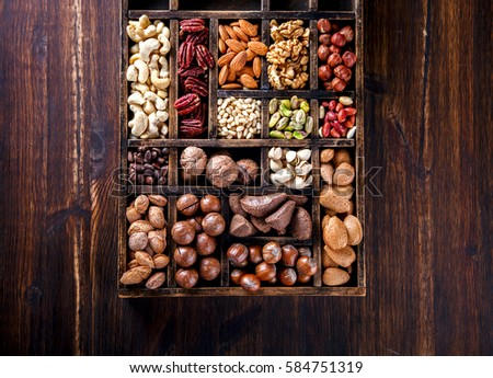 Nuts Mixed in a Wooden Vintage Box.Assortment, Walnuts,Pecan,Peanuts,Almonds,Hazelnuts,Macadamia,Cashews,Pistachios.Concept of Healthy Eating.Vegetarian.Copy space.selective focus.