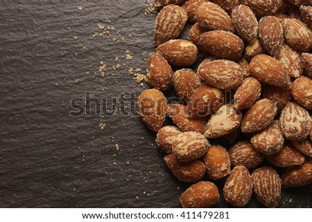 nuts, salted almonds, on a dark background - stock photo