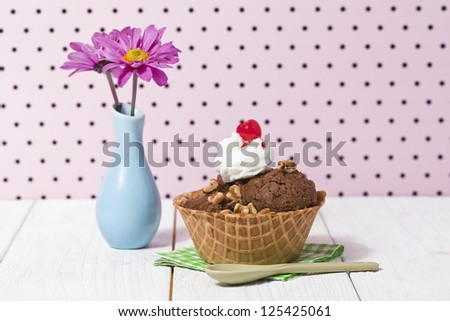 Nutty chocolate ice cream in a big cone with whipped cream and cherry toppings served with napkin and spoon beside a base with flowers - stock photo
