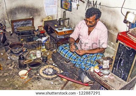 NUWARELIA, SRI LANKA - AUGUST 14: silver smith at work on August 14, 2005 in Nuwarelia, Sri Lanka. People only pay the silver price, craftmansship is just for free. - stock photo