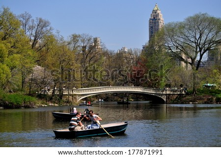 NY - APRIL 24, 2013:  People in rowboats on the Central Park boating lake near the graceful 1864 Bow Bridge on a warm Spring afternoon - stock photo
