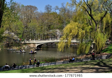 NY - APRIL 24, 2013: The Central Park boating lake and 1864 Bow Bridge with a graceful weeping willow tree - stock photo