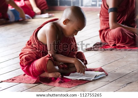 NYAUNG SHWE, MYANMAR  MAY 6: Unidentified novice at Shwe Yan Phe Monastery on May 6, 2012 in Nyaung Shwe, Myanmar.  Boys at 8-20 years old have to enter the Buddhist Order as a novice. - stock photo