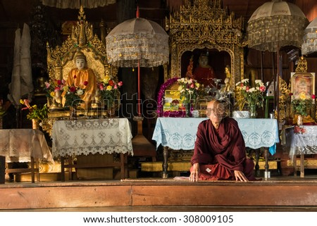 Nyaung Shwe, Myanmar - November 22: A proud buddhist monk in front of the altar in his little remote temple near the town. November 22, 2014 in Nyaung Shwe, Myanmar - stock photo