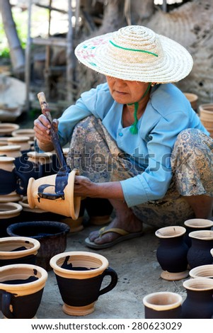 NYAUNG SHWE, SHAN STATE, MYANMAR - JANUARY 12: Burmese craftswoman poses for a photo at work on January 12, 2012 in Nyaung Shwe, Myanmar.