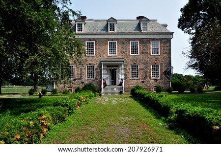 NYC (The Bronx) - 29 July 2014:  South front of high Georgian 1748 Van Cortlandt Manor House built in dressed fieldstone with a double-hipped roof - stock photo