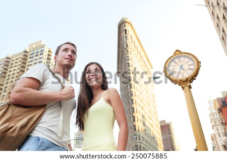 NYC tourism - tourists visiting New York city standing in front of Flatiron building. Young couple of tourists in New York City looking at famous landmark buildings during summer. - stock photo