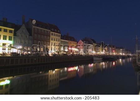 Nyhavn harbour with many bars amd restaurants by night, Copehagen, Denmark - stock photo