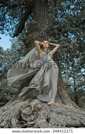 nymph and tree, woman in gown of silk. Jewelry made from shells of sea snails and sea shells. - stock photo