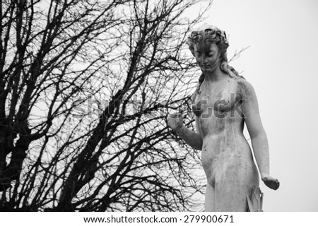 Nymphe marble statue in Tuileries gardens in cloudy winter day. Aged photo. Black and white. - stock photo