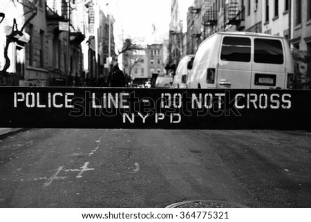 NYPD police line, do not cross against a street/ NYPD police line, do not cross/ New York, USA - January 19, 2016: Police line, do not cross sign against a street in New York with cars parked - stock photo
