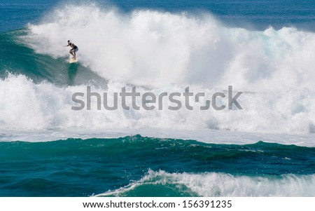 OAHU, HAWAII - JANUARY 2, 2012: a surfer on the North Shore of Oahu, Hawaii.  In the winter, surfers travel from afar to take advantage of swells originating in the stormy North Pacific. - stock photo