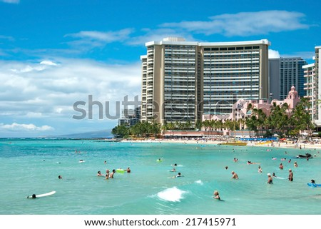 OAHU, HI - SEPTEMBER 19, 2011 - Tourist sunbathing and surfing on Waikiki beach September 19, 2011 in Oahu. Waikiki beach is beachfront neighborhood of Honolulu, best known for white sand and surfing - stock photo