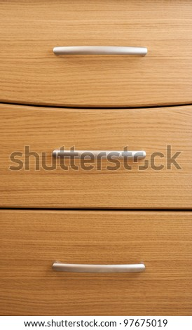 Oak cabinet background.  Detail of wooden chest of drawers in a modern room - stock photo