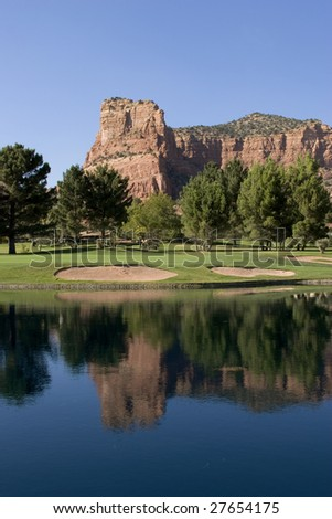oak creek country club, hole 13 red rock reflection in the water - stock photo