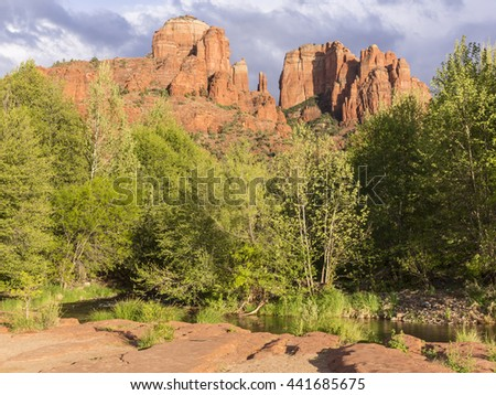 Oak Creek floats quietly below Cathedral Rock Buttes in Red Rock Cross-Crescent Moon Park in Sedona, Arizona - stock photo