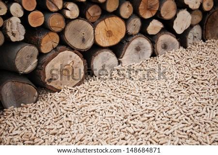 Oak pellets in front wooden wall - stock photo