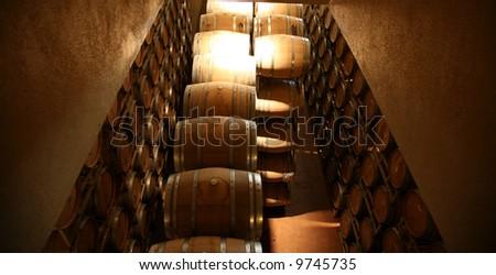 Oak Wine Barrels in a Winery in Napa California, fermenting wine for future drinking pleasure around the world - stock photo