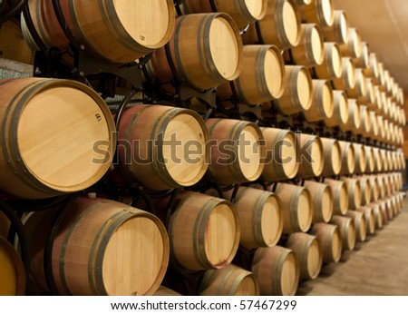 Oak wine barrels stacked up in a winery aging room - stock photo