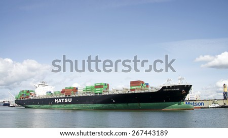OAKLAND, CA - APRIL 06, 2015: Cargo Ship HATSU COURAGE departing the Port of Oakland. Thousands of cargo carriers ply the worlds seas and oceans each year, handling the bulk of international trade.