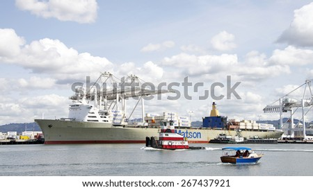 OAKLAND, CA - APRIL 06, 2015: Cargo Ship MANOA docked at the Port of Oakland Middle Harbor. Many vessels, recreational, naval and port authority, travel through the middle harbor past the Port.