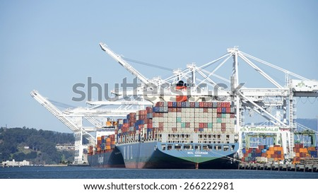 OAKLAND, CA - APRIL 04, 2015: Cargo Ships MOL COURAGE and Hapag-Lloyd OAKLAND EXPRESS loading at the Port of Oakland. The Port of Oakland is the fifth busiest container port in the United States. - stock photo