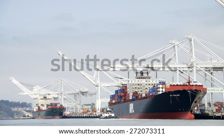 OAKLAND, CA - APRIL 22, 2015: Two Cargo Ships docked at the Port of Oakland. The port loads and discharges more then 99 percent of containerized goods moving through Northern California.