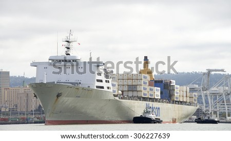 OAKLAND, CA - AUGUST 10, 2015: Matson Cargo Ship MANOA with tugboats SANDRA HUGH and REVOLUTION assisting the vessel to maneuver into the Port of Oakland.
