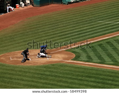 OAKLAND, CA - AUGUST 4: Royals vs. Athletics: Kurt Suzuki places a tag on runner Mike Aviles as he touches homeplate with umpire about to making the call. August 4 2010 at Coliseum in Oakland CA. - stock photo