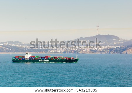 """Oakland, CA - August 28, 2008:  San Francisco Bay, the Evergreen ship """"Ever Decent"""" heading out to sea  with Sutro tower in the background  - stock photo"""