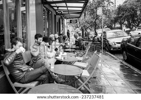 OAKLAND, CA-DEC 11, 2014: Coffee drinkers at a sidewalk cafe in the north Oakland neighborhood of Rockridge, an area known for cafes and upscale restaurants. - stock photo