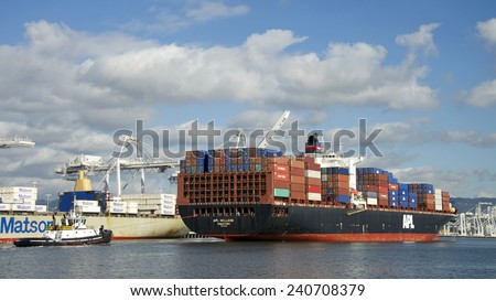 OAKLAND, CA - DECEMBER 29, 2014:  American President Lines (APL) Container ship APL HOLLAND entering the Inner Harbor at the Port of Oakland with Tugboat DELTA CATHRYN following at the Stern. - stock photo