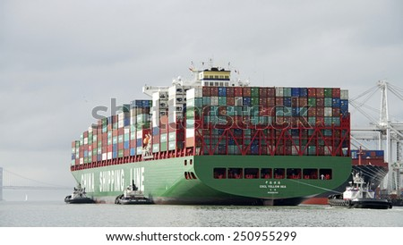 OAKLAND, CA - FEBRUARY 07, 2015: CSCL Cargo Ship YELLOW SEA entering the Port of Oakland with four Tugboats assisting. Tugboats are vital for safe, efficient entry and exit for the large ships.