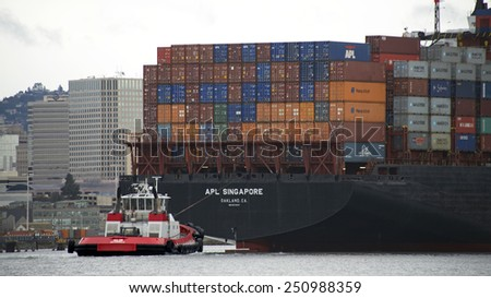 OAKLAND, CA - FEBRUARY 08, 2015: Tugboat VALOR assisting APL Cargo Ship SINGAPORE depart the Port of Oakland. Tugboats are vital for safe, efficient entry and exit for the large ships.