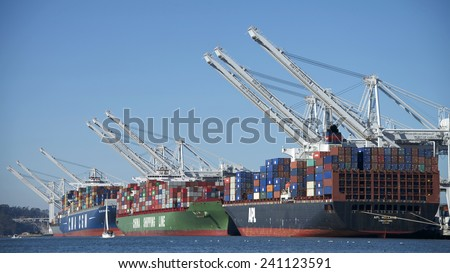 OAKLAND, CA - JANUARY 01, 2015: Cargo ship being loaded at the Port of Oakland, the fifth busiest container port in the United States, behind Long Beach, Los Angeles, Newark, and Savannah. - stock photo