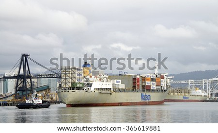 OAKLAND, CA - JANUARY 18, 2016: Matson Cargo Ship MAUI entering a turning basin at the Port of Oakland. Tugboats will turn the vessel prior to docking at the Port.