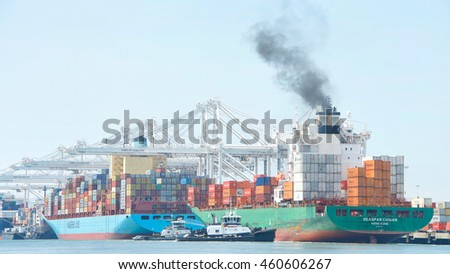 Oakland, CA - July 27, 2016: Cargo Ships today are larger than their predecessors, and are unable to maneuver sideways. Tugboats push SEASPAN CHIWAN sideways to the dock at the Port of Oakland.