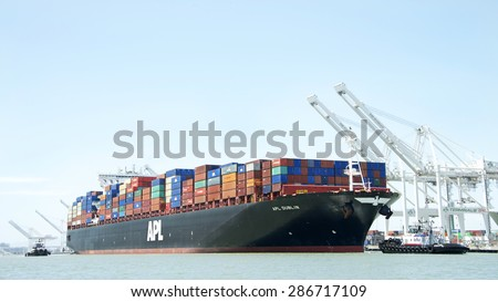 OAKLAND, CA - JUNE 04, 2015: APL Cargo Ship DUBLIN, loaded with shipping containers, required four tugboats to pull the vessel away from the dock at the Port of Oakland.