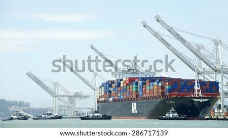 OAKLAND, CA - JUNE 04, 2015: Cargo Ships are unable to maneuver sideways. Tugboats REVOLUTION, PATRICIA ANN, AHBRA FRANCO and Z-FIVE pull APL DUBLIN away from the dock to depart the Port of Oakland.