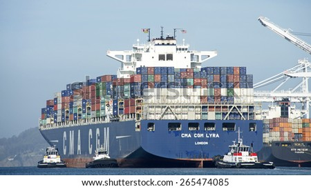 OAKLAND, CA - MARCH 30, 2015: CMA CGM Cargo Ship LYRA entering the Port of Oakland with tugboat assistance. Tugs move vessels that should not move themselves, such as ships in a crowded harbor. - stock photo