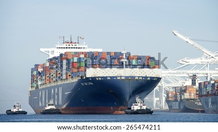 OAKLAND, CA - MARCH 30, 2015: GMA CGM LYRA entering the Port of Oakland. Five tugboats assist the massive vessel maneuver. Tugboats are vital for safe, efficient entry and exit for the large ships. - stock photo