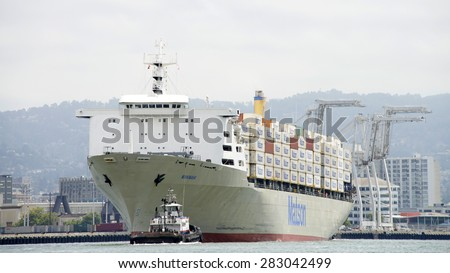 OAKLAND, CA - MAY 27, 2015:  AmNav Tugboat LIBERTY at the bow of Matson Cargo Ship MAHIMAHI, assisting the vessel to maneuver into the Port of Oakland.