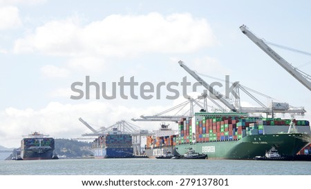 OAKLAND, CA - MAY 13, 2015:  Cargo Ship HANJIN BUDDAH  entering the Port of Oakland as EVER LIBRA prepares for departure. The Port of Oakland is the fifth busiest container port in the United States.