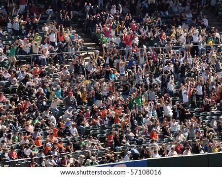 OAKLAND, CA - MAY 23: San Francisco Giants Vs. Oakland Athletics: Oakland Athletics fans do the wave during the late innings to stay entertained.  Taken May 23 2010 at the Coliseum Oakland California. - stock photo