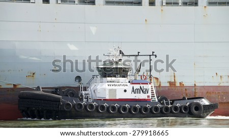 OAKLAND, CA - MAY 14, 2015:t REVOLUTION assisting a cargo ship into the Port of Oakland. American Navigation was a pioneer in developing tugboats with high horsepower engines in relatively small hulls - stock photo