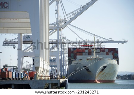 OAKLAND, CA - NOVEMBER 17, 2014: A China Ocean Shipping Company, (COSCO) Cargo ship loading at the Port of Oakland. Cosco is the largest dry bulk carrier in China. - stock photo