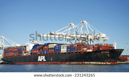 OAKLAND, CA - NOVEMBER 17, 2014: APL Cargo Ship loading new cargo at the Port of Oakland.  American President Lines Ltd. (APL) is the world's seventh-largest container  shipping company in the world.