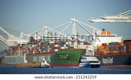 OAKLAND, CA - NOVEMBER 17, 2014: China Ocean Shipping (COSCO), China Shipping Container lines and Hapag-Lloyd Cargo Vessels loading shipping containers at the Port of Oakland on a busy Monday Morning. - stock photo